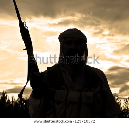 Silhouette of muslim rebel with rifle - stock photo