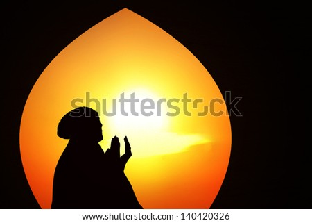 Silhouette of muslim woman inside the mosque on orange background - stock photo