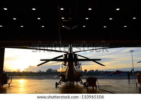 silhouette of offshore oil rig  helicopter in the hangar next to runway with sunrise background . - stock photo
