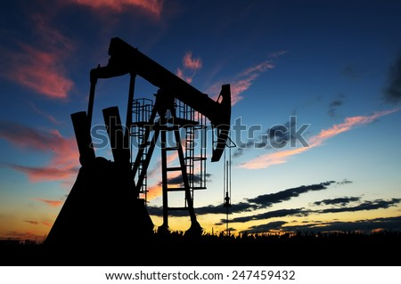 Silhouette of oil pump at dawn sky background - stock photo