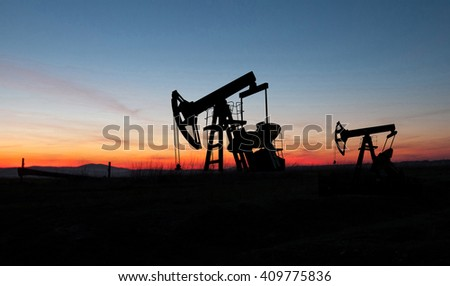 silhouette of oil pumps from oil field - stock photo