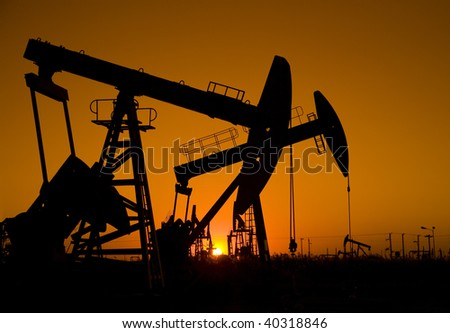 Silhouette of oil rigs with sunset - stock photo