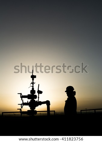 Silhouette of oilfield worker at wellhead in oilfield - sunset - Black and white  - stock photo