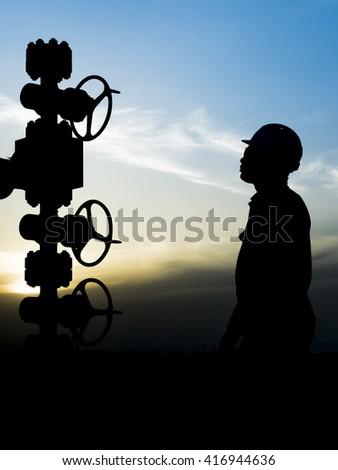 Silhouette of oilfield worker monitoring wellhead controls in oilfield - stock photo