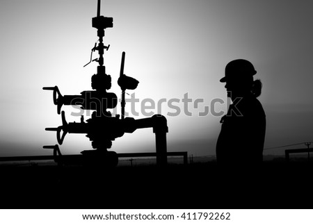 Silhouette of oilfield worker next to wellhead in oilfield - sunset - Black and white - stock photo