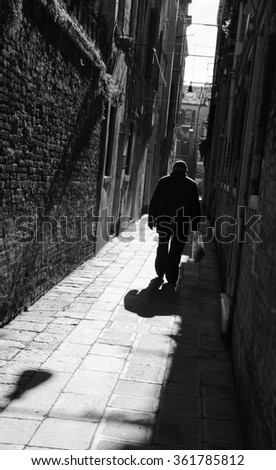 Silhouette of  old man going on narrow street in shining sun rays. (Venice, Italy) A game of light and shadow. Light spots. Aged photo. Black and white. - stock photo