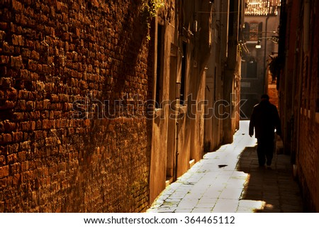 Silhouette of  old man going on narrow street in shining sun rays. (Venice, Italy) A game of light and shadow. Selective focus on the brick wall.  - stock photo