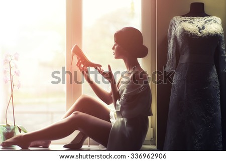 Silhouette of one young beautiful slim brunette woman in underwear sitting and drinking coffee in morning looking at window near white wedding lace dress on mannequin, horizontal picture - stock photo