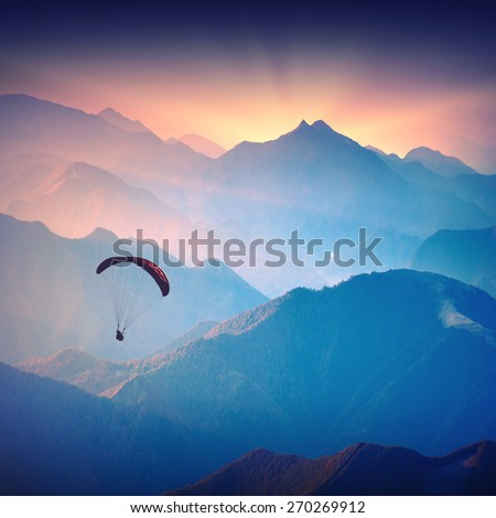 Silhouette of paraglide flying over the high mountains in a light of sunrise. Ukrainian Carpathian valley.  - stock photo
