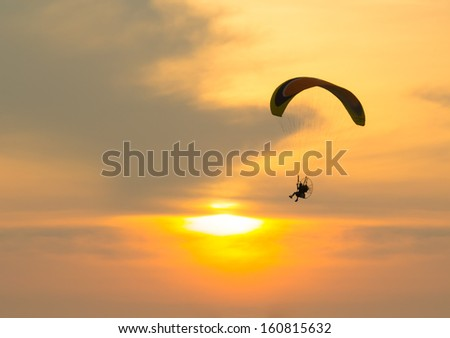 Silhouette of paragliding with sunset background. - stock photo