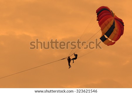 Silhouette of Parasailing in the sky. - stock photo
