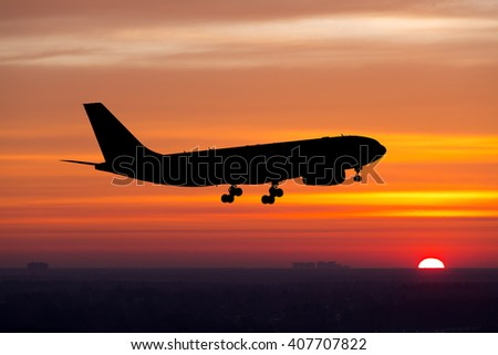 Silhouette of passenger plane. Aircraft is taking off towards the rising sun. - stock photo