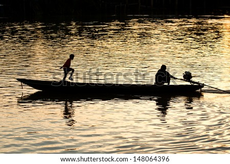 silhouette of people and boat on the river