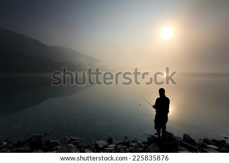 Silhouette of people fishing on the lake with mist at sunrise
