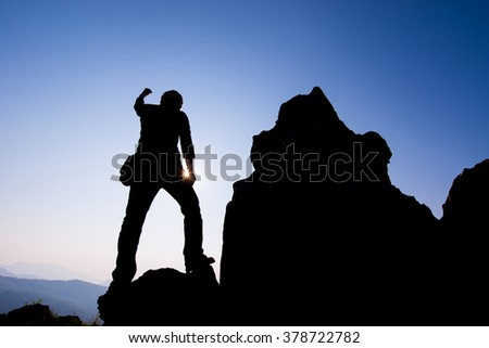 Silhouette of people Hike on the peak mountain at sunset with arms raised up above head in celebration