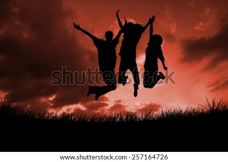 Silhouette of people jumping against red sky over grass - stock photo