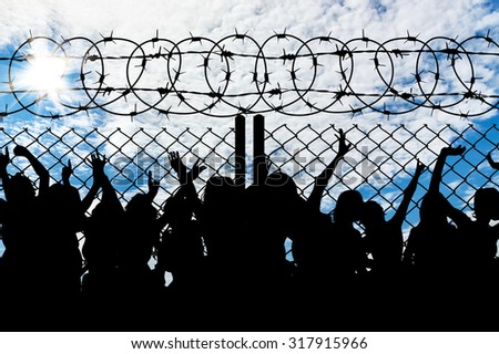 Silhouette of people refugees behind metal bars and barbed wire - stock photo