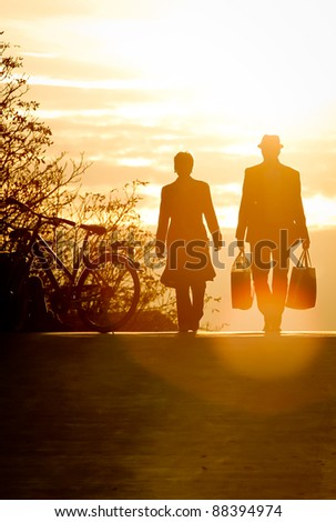 silhouette of people walking in sunset - stock photo