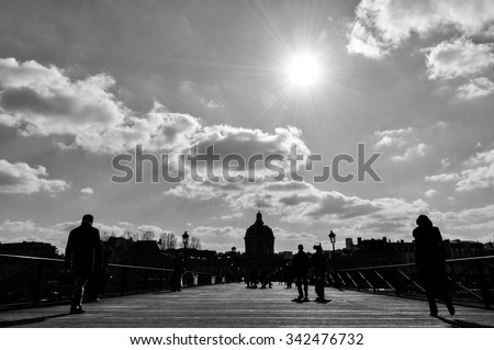 Silhouette of people walking on Pont des Arts in Paris, France. Black and white photograph. - stock photo