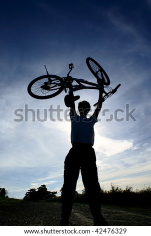 Silhouette of person holding up bike with blue sky and clouds