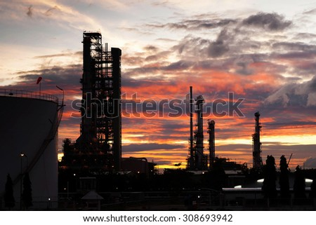 Silhouette of petrochemical industrial plant in sunrise  - stock photo