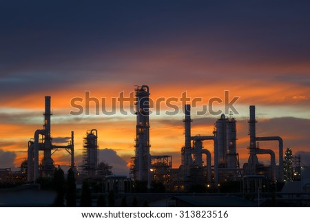 Silhouette of petrochemical plant or Oil and gas refinery at twilight - stock photo