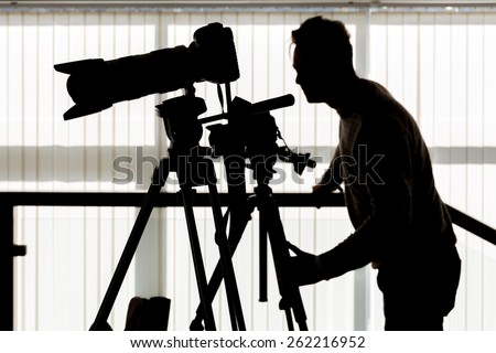 Silhouette of photographer and cameraman shot the video on a tripod at the workplace indoors - stock photo
