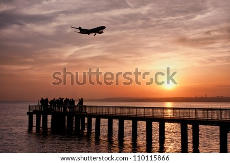 Silhouette of photographer group on pier and plane - stock photo