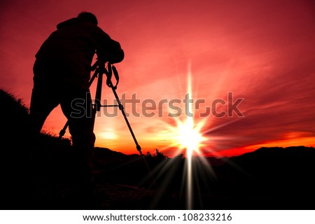 Silhouette of photographer on the top of mountain - stock photo