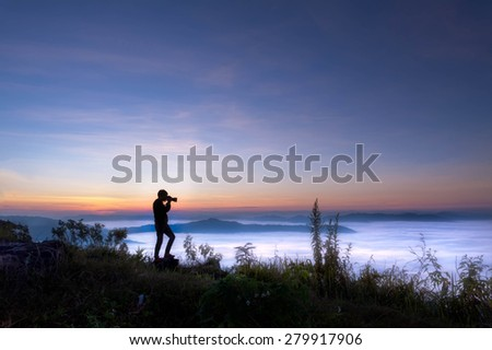 silhouette of photographer taking picture on landscape at doi phatang chiang rai, thailand - stock photo