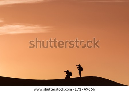 Silhouette of photographers in desert Sahara, Morocco  - stock photo
