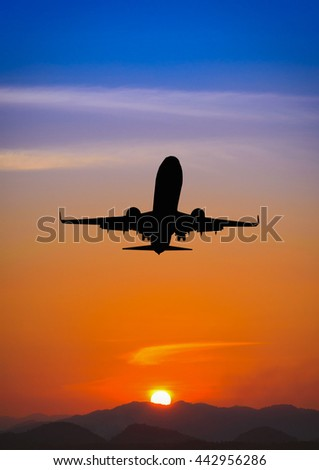 Silhouette of plane fly over the mountain during sunset.