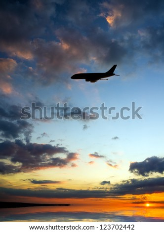 silhouette of plane fly over water during sunrise - stock photo