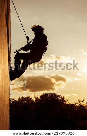 Silhouette of police officer during rope exercises with weapons - stock photo
