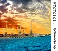 Silhouette of portal cranes in harbor aver the sunset - stock photo