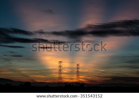 Silhouette of power grid during sunrise. Rays of light is visible at the sky - stock photo