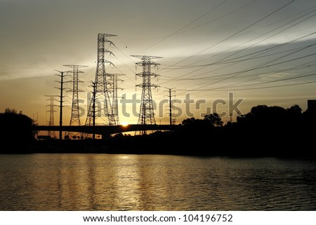 Silhouette of power pylon line from a hydro power plant by a reservoir against a fiery sunset. - stock photo