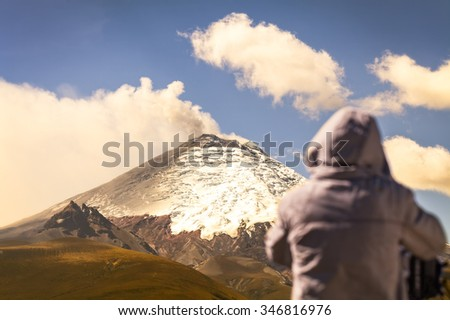 Silhouette of professional photographer posing a powerful day explosion of Cotopaxi volcano, South America  - stock photo