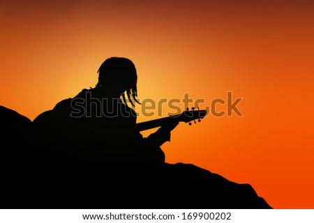 Silhouette of  rasta man playing guitar. - stock photo