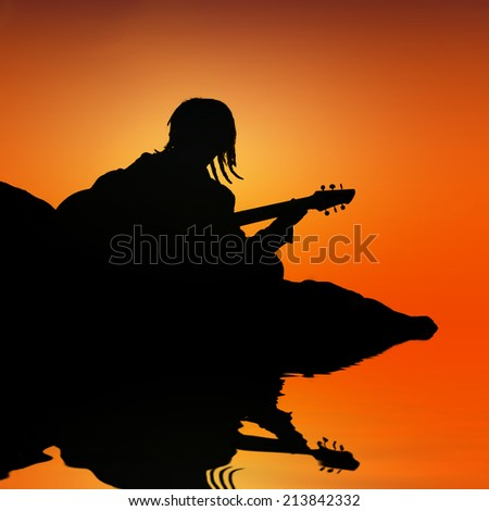 silhouette of rasta man playing guitar with water reflection