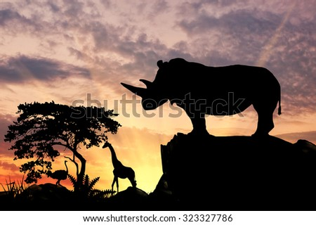 Silhouette of rhino on a hill at sunset savanna - stock photo