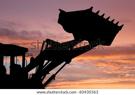 silhouette of risen loader excavator scoop shovel over scenic dawn - stock photo