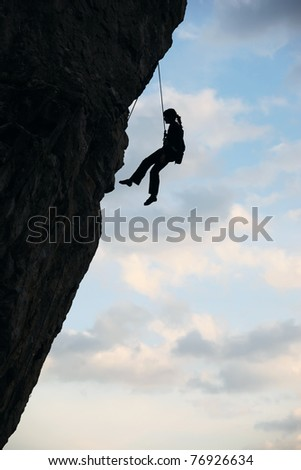 Silhouette of rock climber against cloudy sky background