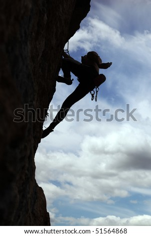 Silhouette of rock climber climbing a cliff with cloudy sky background - stock photo