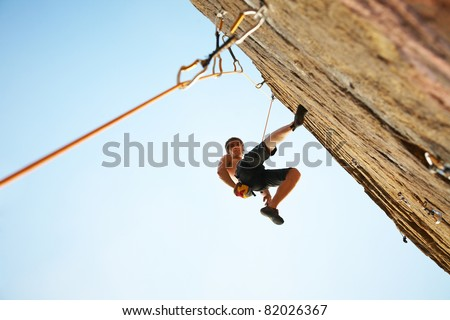 silhouette of rock climber climbing an overhanging cliff against the blue sky - stock photo