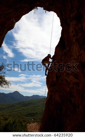 Silhouette of rock climber climbing the cliff - stock photo