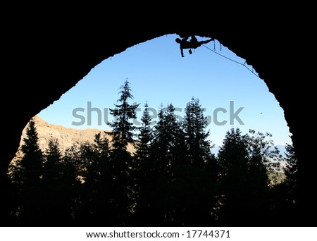 silhouette of rock climber climbing the roof of the pipedream cave, Maple Canyon, Utah - stock photo