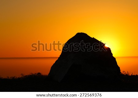 Silhouette of rock with sun - stock photo