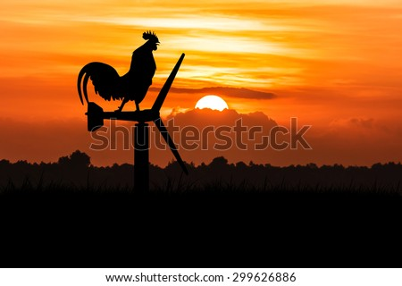 silhouette of roosters crow stand on a wind turbine. In the morning sunrise background - stock photo