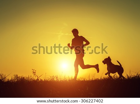 Silhouette of runner with dog  in sunset rise - stock photo